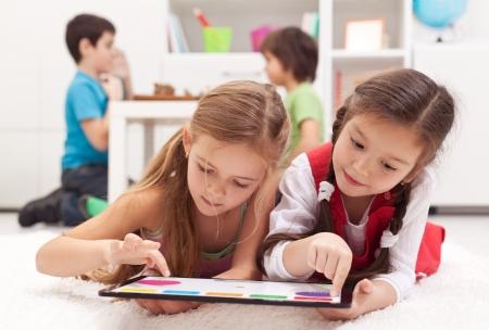 onderwijs: Kleine meisjes spelen op een tablet-pc-apparaat - tot op de vloer