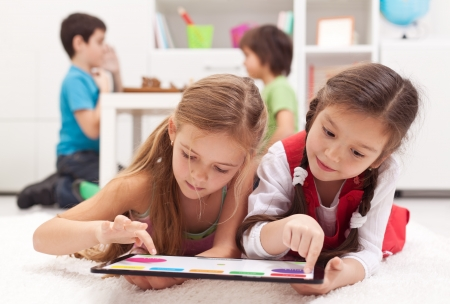 two floors: Little girls playing on a tablet computing device - laying on the floor Stock Photo