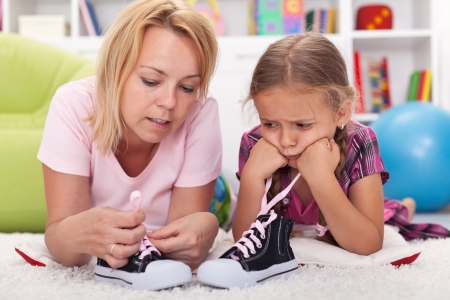 Mother teaching little unhappy girl to tie her shoes showing the process Stock Photo - 17565832