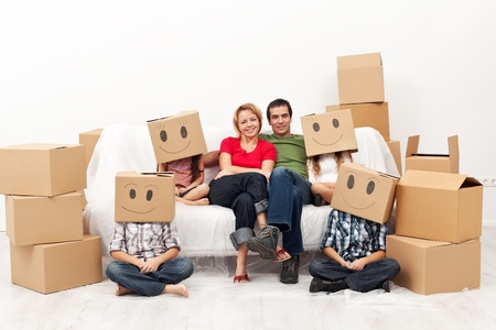 Happy family with four kids in their new home - among cardboard boxes