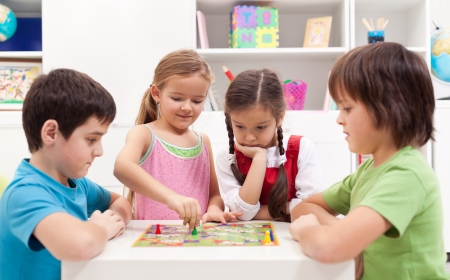 game room: Children playing board game - sitting around a small table Stock Photo