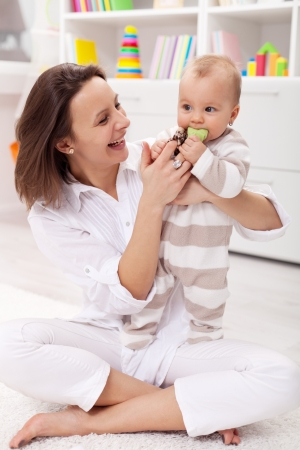 Happy mother with baby girl playing at home photo