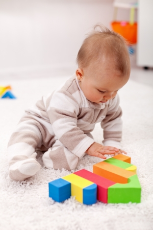 Baby girl playing eith wooden blocks sitting on the floor photo