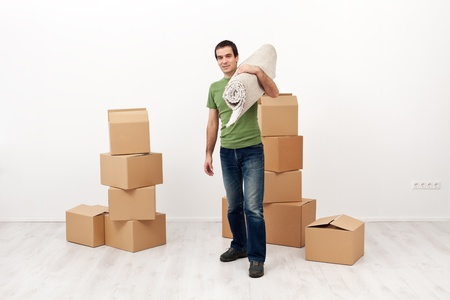 Moving into a new home concept - man carrying carpet roll Stock Photo - 17850670