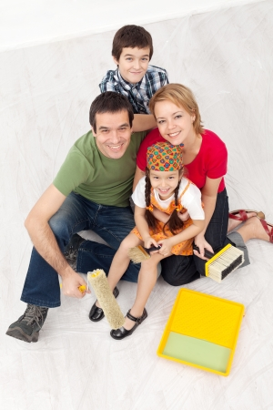 Happy family with paint preparing to redecorate their home - together with the kids photo