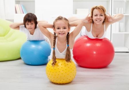 Dzieci i kobieta robi gimnastyka w domu - z dużymi kulkami Zdjęcie Seryjne