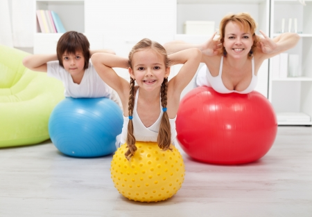 Kids and woman doing gymnastic at home - with large balls