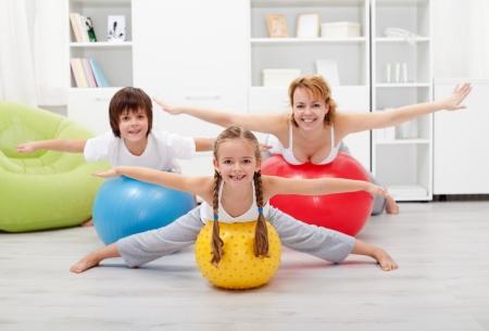 행복 한 아이는 큰 고무 공을 사용하여 자신의 어머니와 함께 운동 스톡 콘텐츠