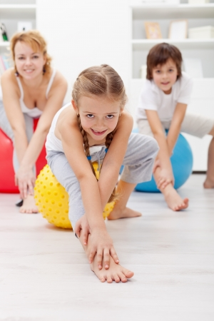 kids exercise: Gymnastic at home - woman and kids using large exercise balls