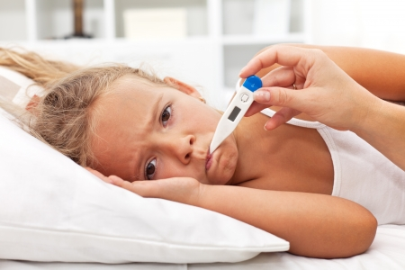 caucasian fever: Sick little girl holding thermometer laying in bed with grumpy face