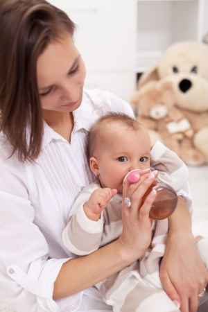 Caring mother feeding baby girl with bottle photo