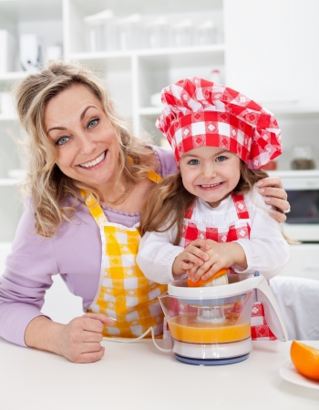 Happy woman and child making fresh orange juice in the kitchen photo