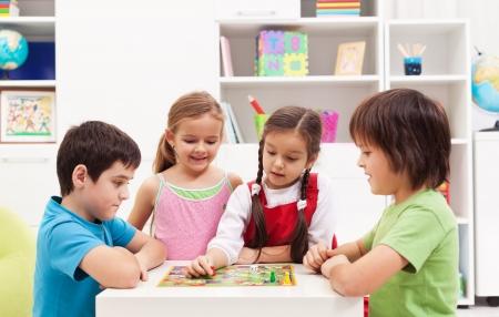Cztery dzieci bawi gry planszowe w pokoju