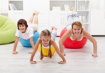 Happy people using large exercise balls - doing gymnastic at home