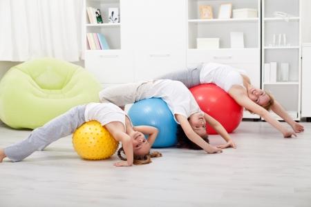 Dzieci i kobieta robi ćwiczenia rozciągające - korzystania z dużych kulek