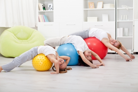 Kids and woman doing stretching exercises - using large balls Foto de archivo