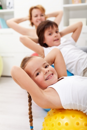 Kids exercising with their mother using gymnastic balls