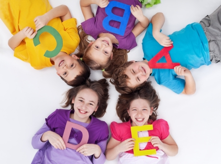 primary colours: Happy school kids with colorful alphabet letters laying in circle on the floor