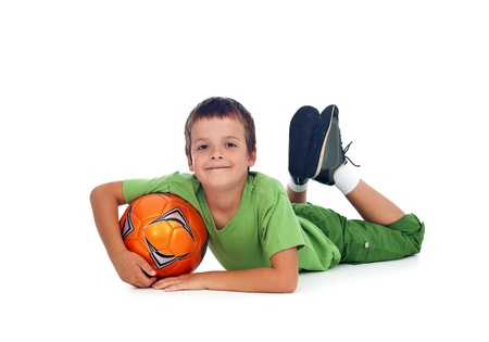 Happy boy with soccer ball laying on the floor - isolated photo