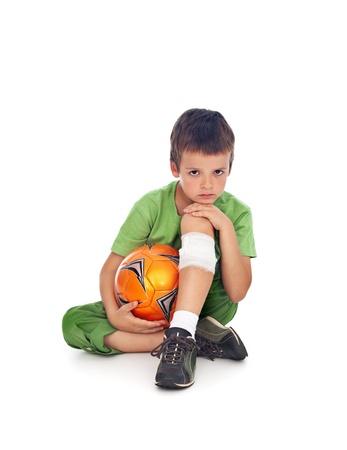 Boy with injured leg holding a soccer ball Standard-Bild