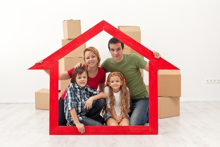 Happy family in their new home - with house shaped frame and cardboard boxes Stock Photo - 18162517