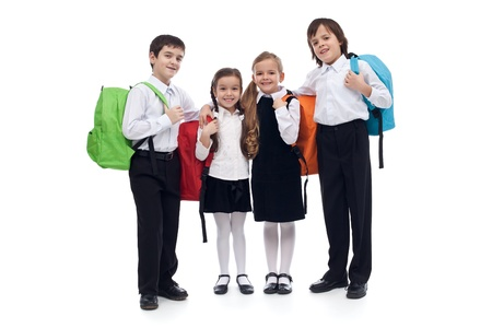 Happy elementary school kids with colorful back packs - isolated photo