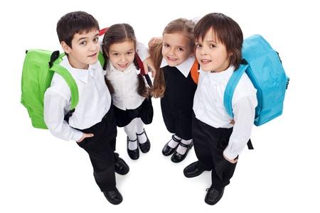 Glückliche Schulkinder mit Rucksäcken - halten einander, suchen up - isoliert Standard-Bild - 18162510