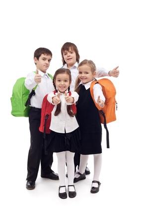 Szczęśliwa grupa dzieci ze szkoły podstawowej z thumbs up - izolowane