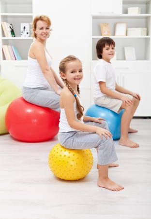ball stretching: Happy family - woman and kids - exercising at home using gymnastic balls