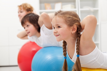 fit ball: Kids and woman doing gymnastic exercises with balls - stretching their back