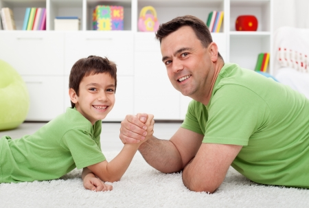 health education: Father arm wrestling with his boy - happy family time together Stock Photo