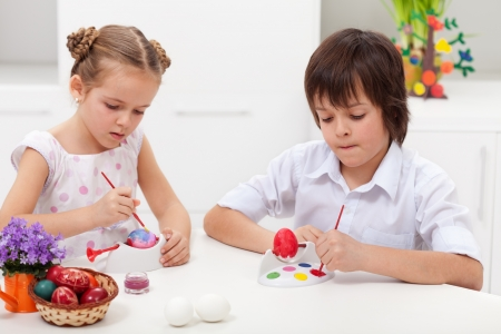 creative egg painting: Children painting easter eggs sitting at the table