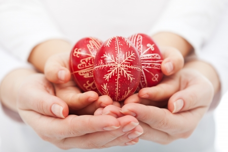 Woman and child hands holding traditional red easter eggs