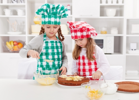 niños cocinando: Niñas con sombreros de chef preparando un pastel en la cocina Foto de archivo