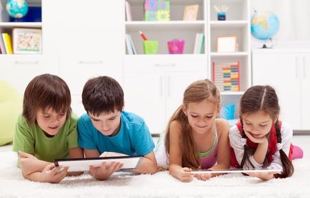Kids mit modernen Tablet-Computer auf dem Boden Standard-Bild - 18494341