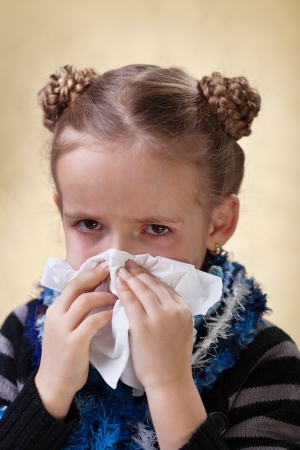 Little girl with the flu having red eyes - blowing nose photo