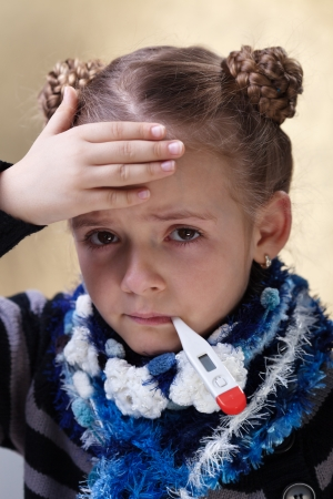 grippe: Little girl having the flu - checking temperature with hand and thermometer