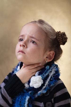 angina: Niña con dolor de garganta en la temporada de gripe tocando su cuello