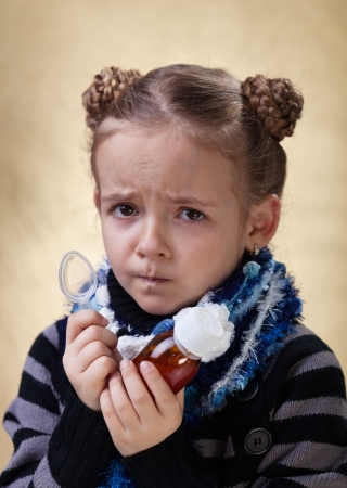 cough medicine: Little girl with the flu - holding cough medicine syrup and looking unhappy Stock Photo