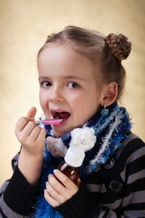 cough medicine: Little girl with warm clothes taking cough medicine syrup Stock Photo