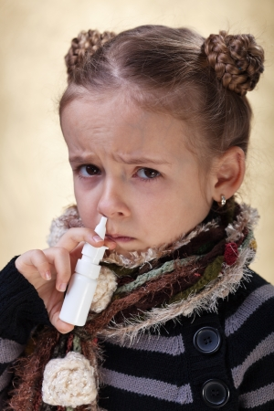 Little girl with the flu using nasal spray reluctantly photo