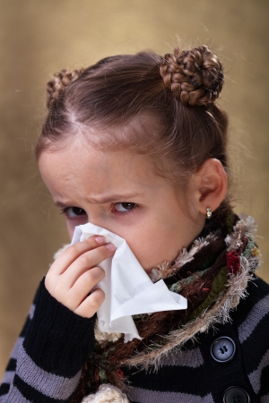 Little girl in flu season - wearing warm clothes and blowing nose photo
