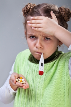 Sick little girl with the flu - holding pills and thermometer Stock Photo - 18494325