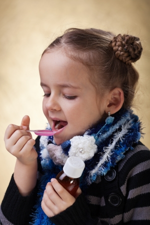 Young girl taking cough medicine syrup photo