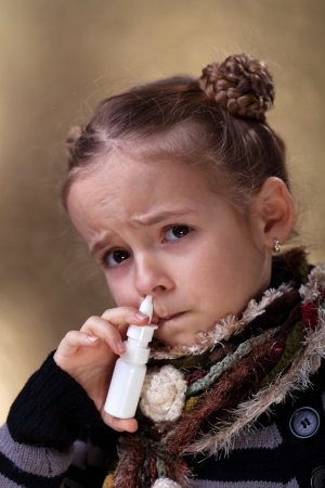 Young girl using nasal spray looking worried photo