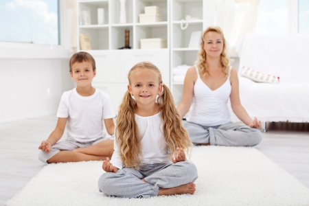 Kids doing yoga relaxing exercise with their mother at home photo