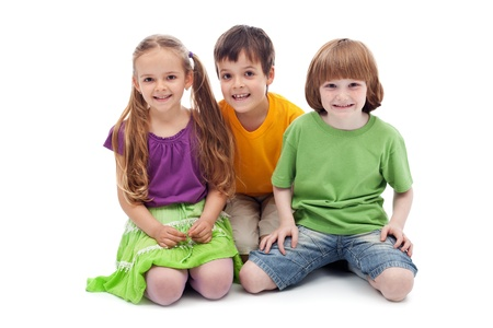 Happy kids sitting on the floor smiling - isolated
