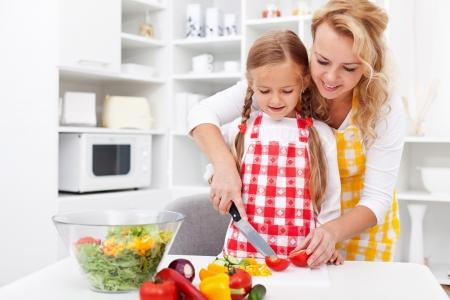 여자와 어린 소녀는 부엌에서 야채 샐러드를 준비 스톡 콘텐츠
