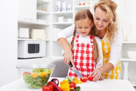 kitchen apron: Woman and little girl preparing a vegetables salad in the kitchen Stock Photo