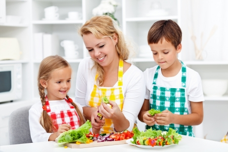 family kitchen: Salad time with the kids in the kitchen - healthy life education Stock Photo